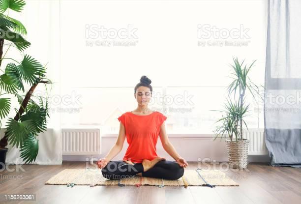 Aantrekkelijke Jonge Vrouw Oefenen En Zittend In Yoga Lotus Positie Terwijl Rust Thuis Stockfoto en meer beelden van 20-29 jaar
