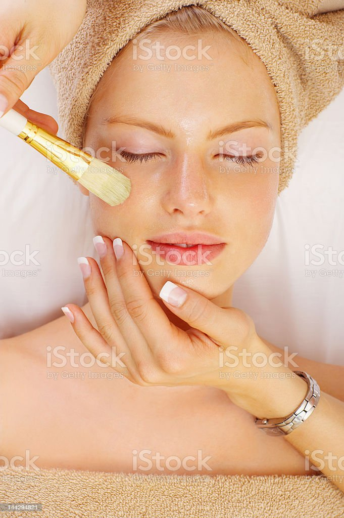Attractive young woman getting a facial royalty-free stock photo