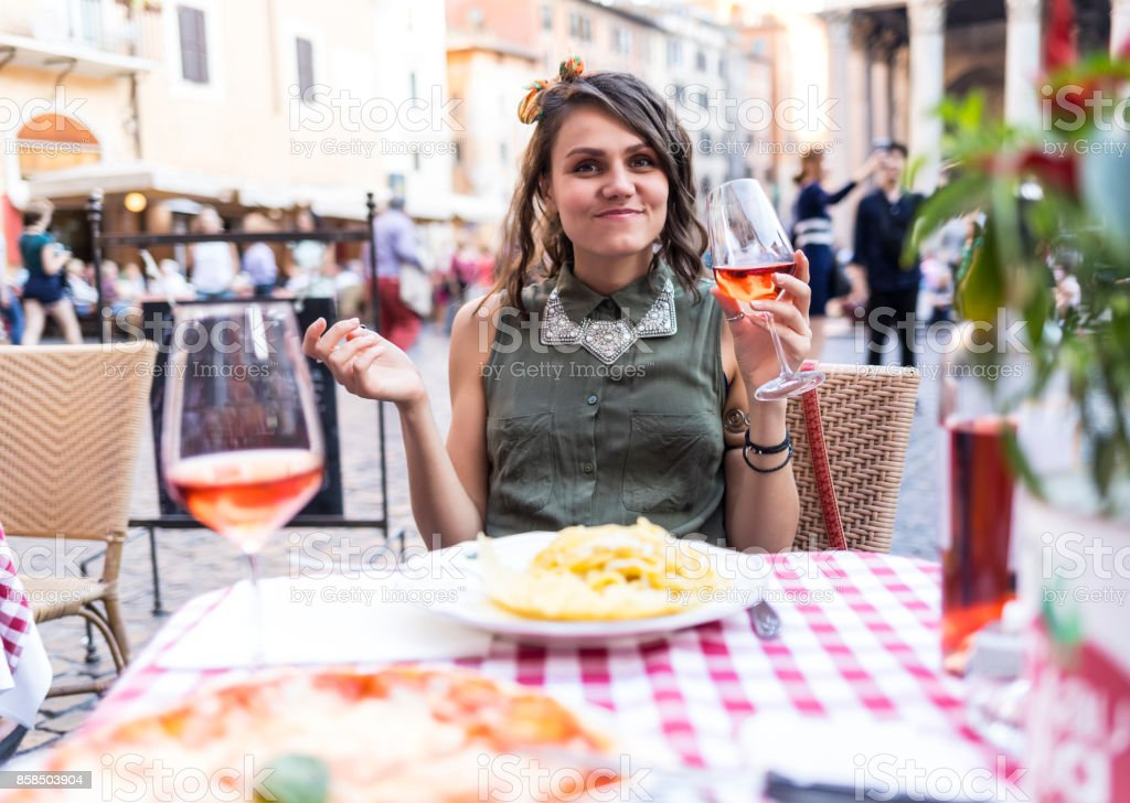 Attractive young woman having meal in Rome stock photo