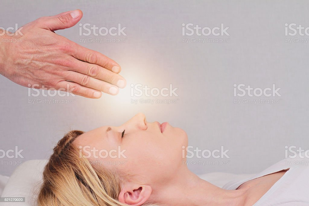 Attractive young woman having reiki healing treatment stock photo