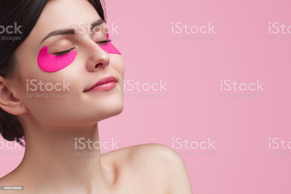 Attractive young woman having under eye mask royalty-free stock photo