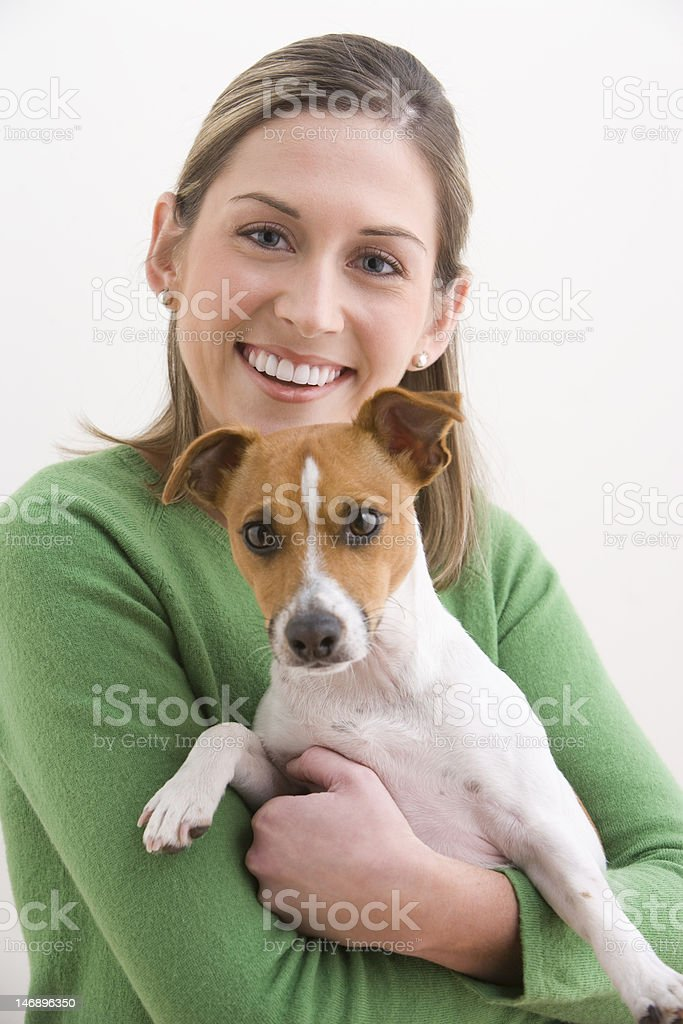 Attractive Young Woman Holding A Dog And Smiling stock photo