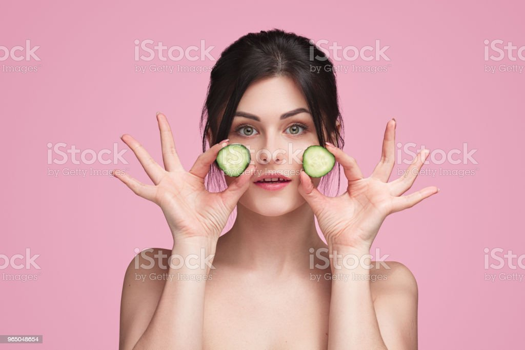 Attractive young woman holding cucumber slices zbiór zdjęć royalty-free