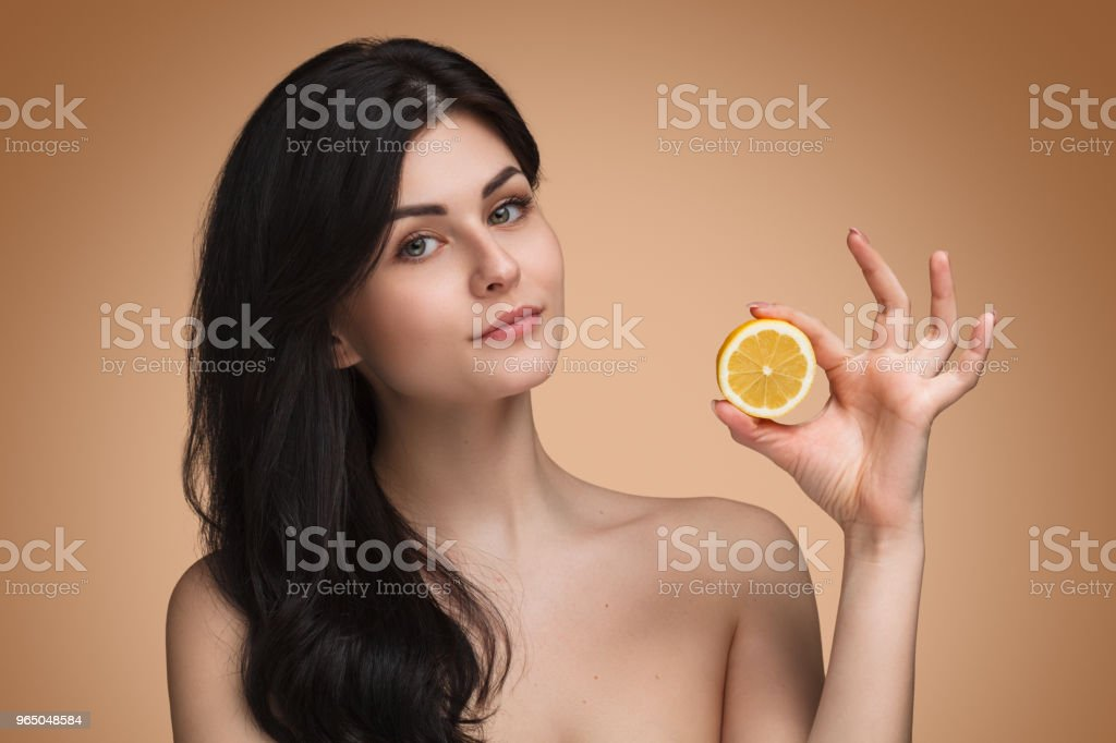 Attractive young woman holding orange slice royalty-free stock photo