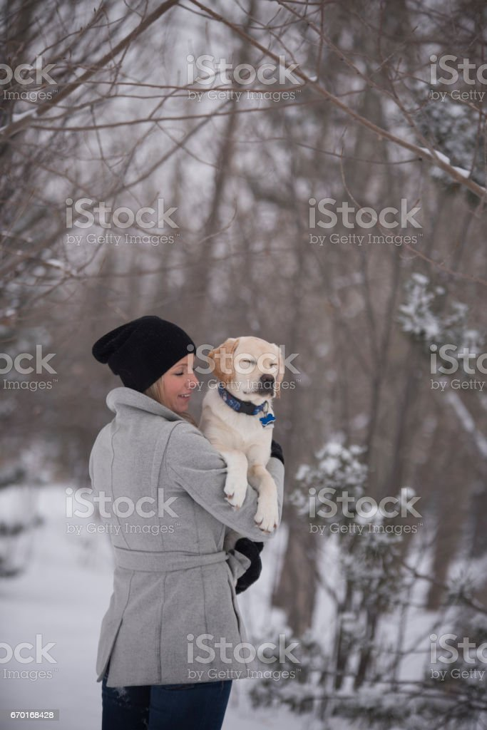 Attractive young woman holding yellow lab puppy and both her and the puppy have their eyes closed stock photo