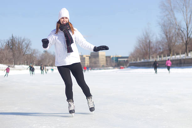 Attractive young woman ice skating during winter stock photo