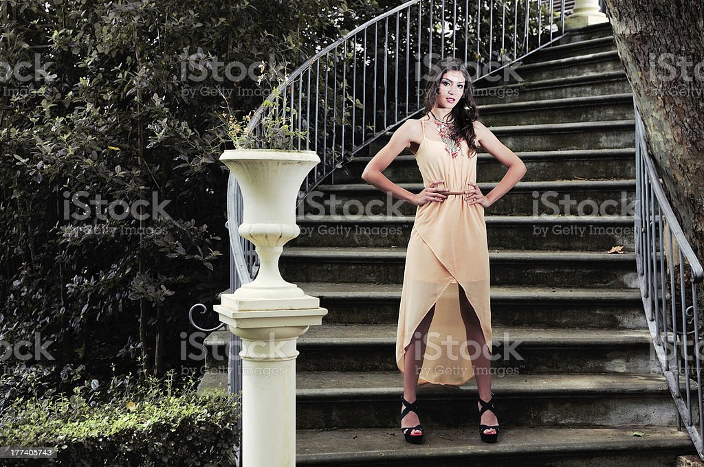 Attractive young woman in a garden stairs stock photo