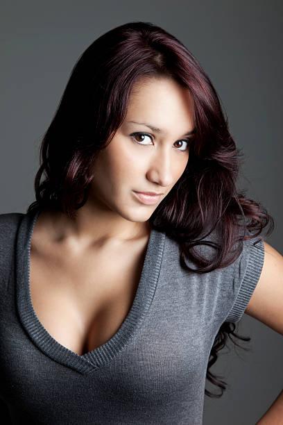 attraktive junge frau in grauer pullover - rotes oberteil stock-fotos und bilder