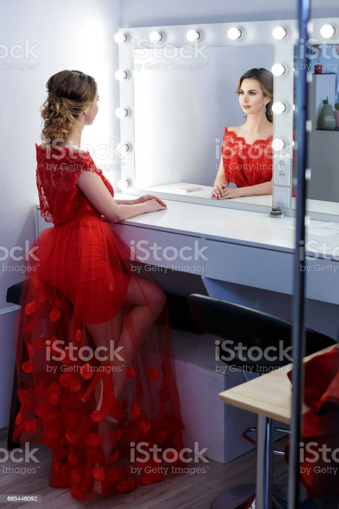 attractive young woman in red dress is prepared in dressing room foto de stock royalty-free
