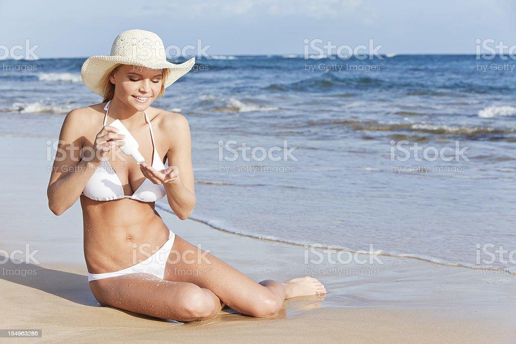 Attractive Young Woman in White Bikini Applying Sunscreen royalty-free stock photo