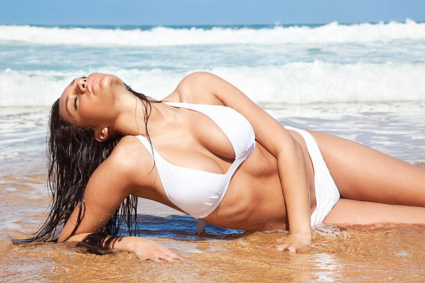 attractive young woman in white bikini posing on hawaiian beach - busty women in bikinis stock pictures, royalty-free photos & images