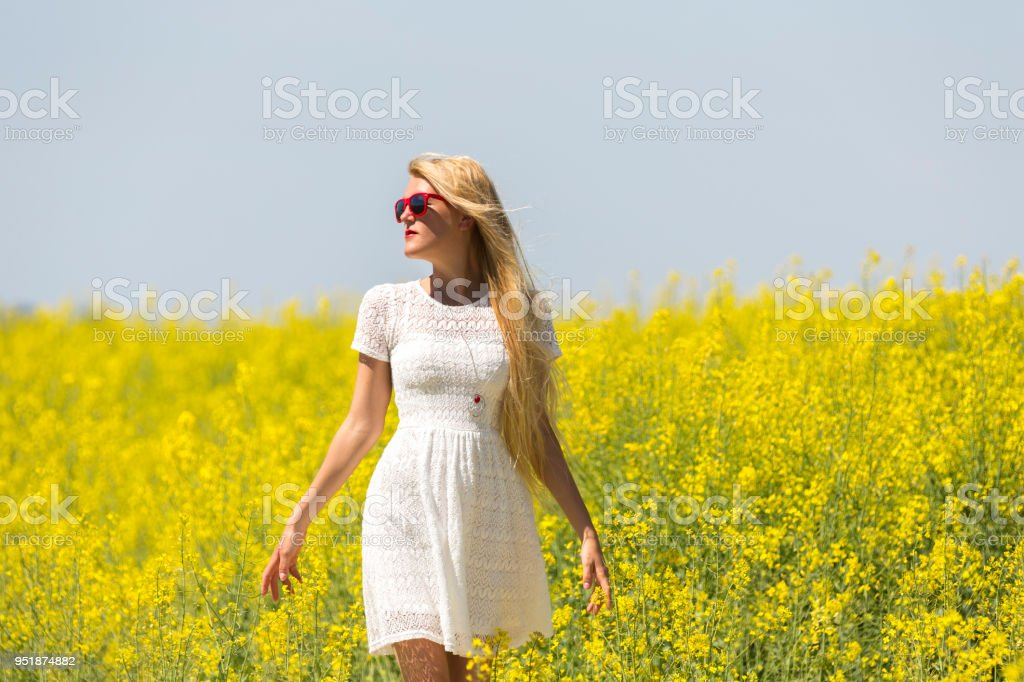 Attractive young woman in white drees walking though canola field stock photo