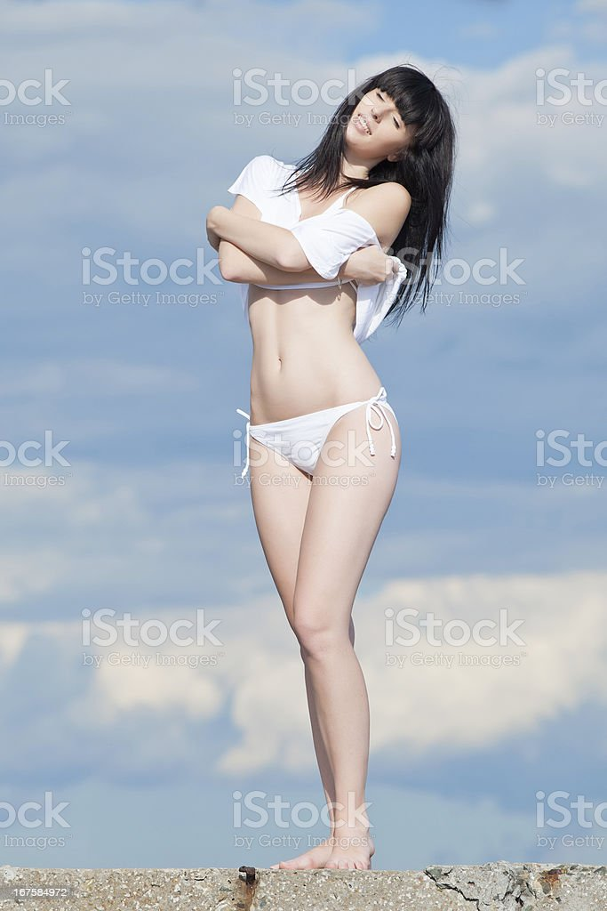 Attractive young woman in white on background of cloudy sky royalty-free stock photo