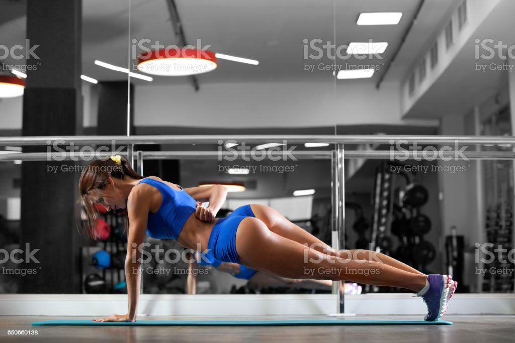 Attractive young woman is doing plank exercise while working out in gym stock photo