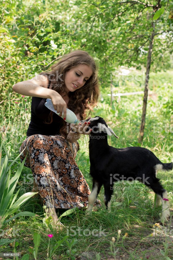 Attractive young woman is feeding a baby goat with milk - Photo