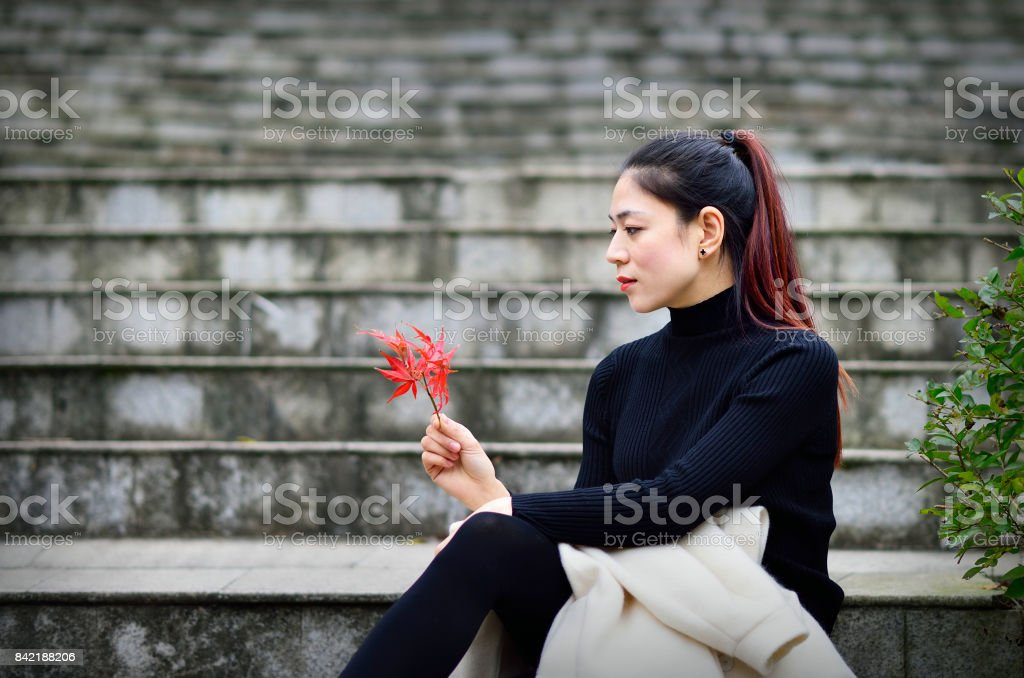 Attractive young woman is sitting on the steps of the outdoor stock photo