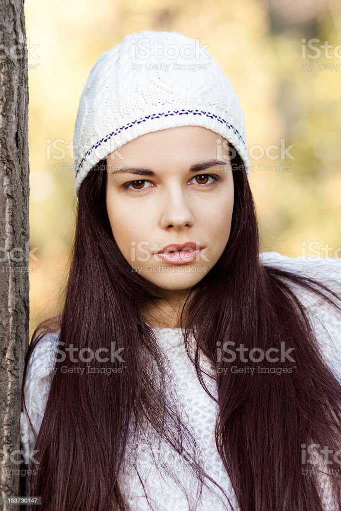 Attractive young woman, leaning on tree in park royalty-free stock photo