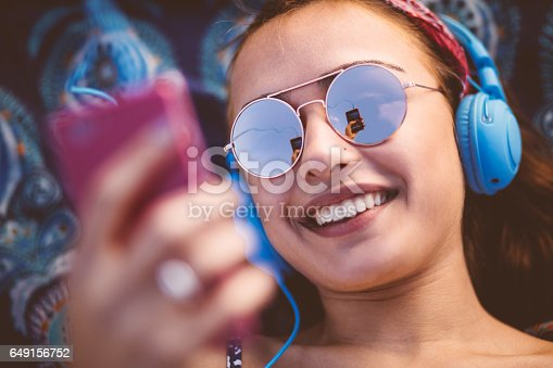 Beautiful young hipster woman wearing sunglasses and headphones, listening to music, texting and smiling