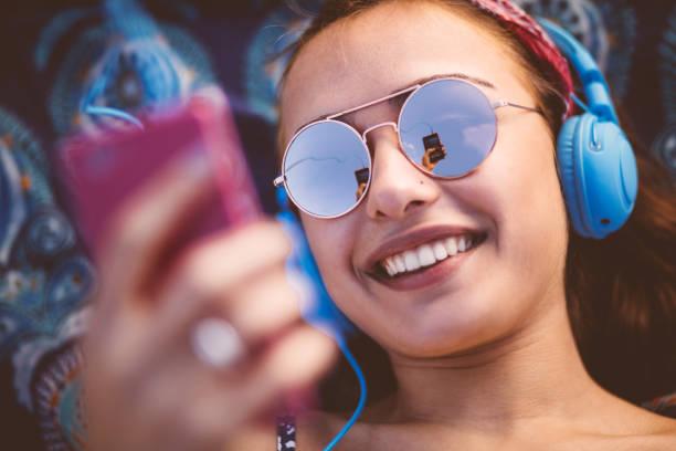 atractiva mujer joven escuchando música en su teléfono inteligente - auriculares equipo de música fotografías e imágenes de stock
