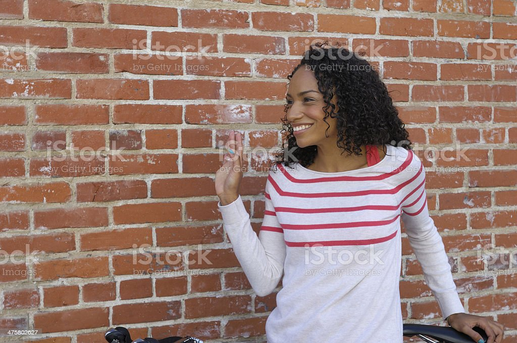 Attractive Young Woman Looking and Waving to the Side royalty-free stock photo