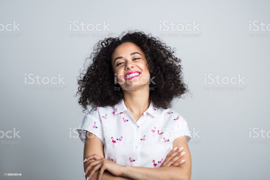 Attractive young woman looking confident Portrait of attractive young woman with curly hair standing with her arms crossed on gray background 20-24 Years Stock Photo