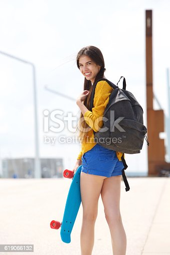 istock Attractive young woman looking over shoulder with skateboard 619066132