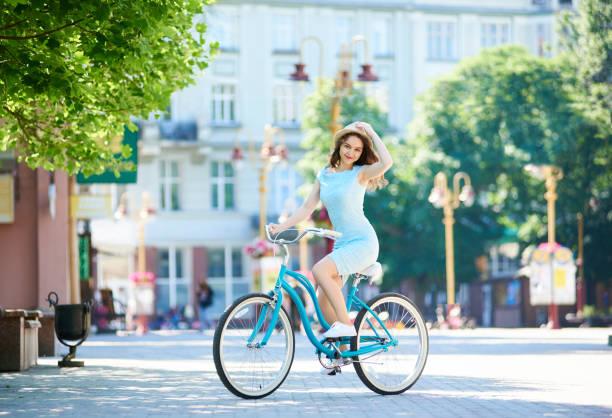 Belle jeune femme à la recherche à la caméra, tenant son chapeau de paille tout en vélo bleu le long du centre de la ville pavée sur journée d'été. Mode de vie heureux arrière-plan flou assez féminin vélo turquoise - Photo