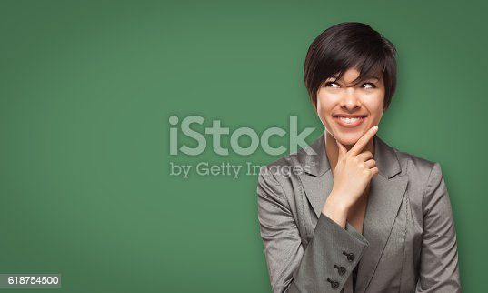 istock Attractive Young Woman Looking Up to Blank Chalk Board 618754500