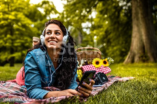 Beautiful young female lying on a picnic blanket in park and listening to music on smartphone