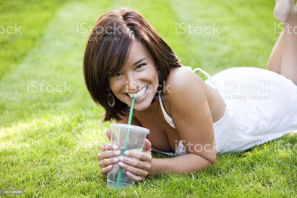 Attractive Young Woman Lying on Grass royalty-free stock photo