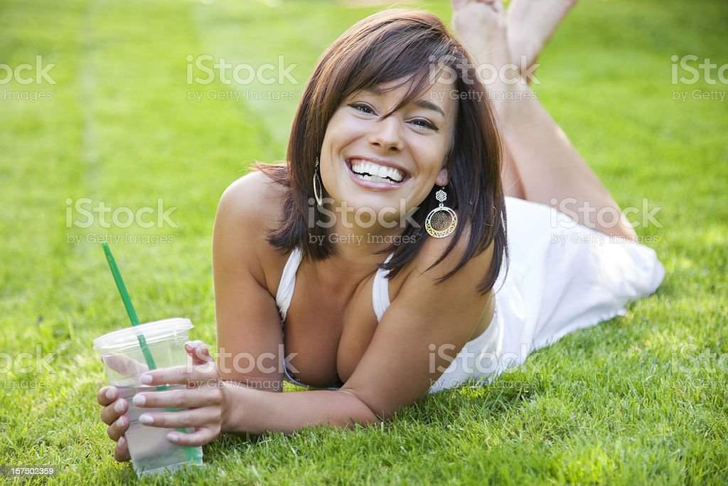 Attractive Young Woman Lying on Grass with Cold Beverage stock photo
