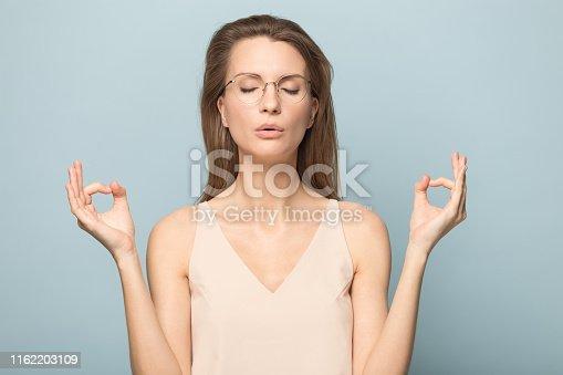 916126594istockphoto Attractive young woman making mudra gesture portrait. 1162203109