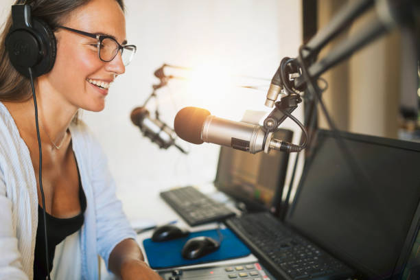 Attractive Young Woman Making Online Podcast Radio Talk Show Attractive young millennial woman in front of microphone, using headphones, making an online radio podcast talk show. radio dj stock pictures, royalty-free photos & images