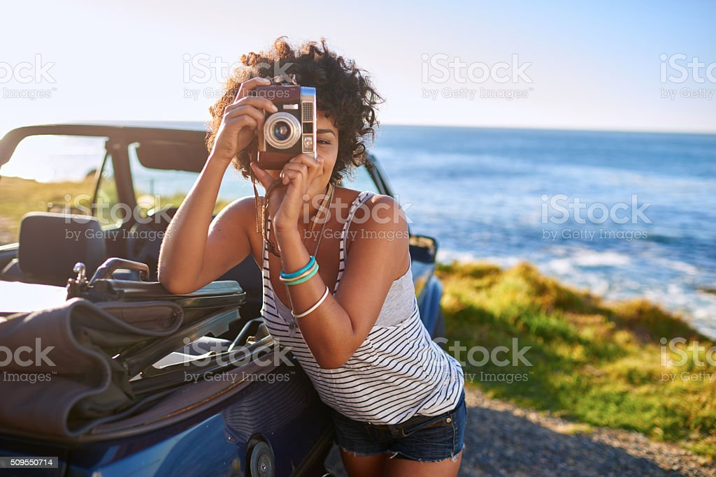 Attractive young woman near car taking pictures with old camera stock photo