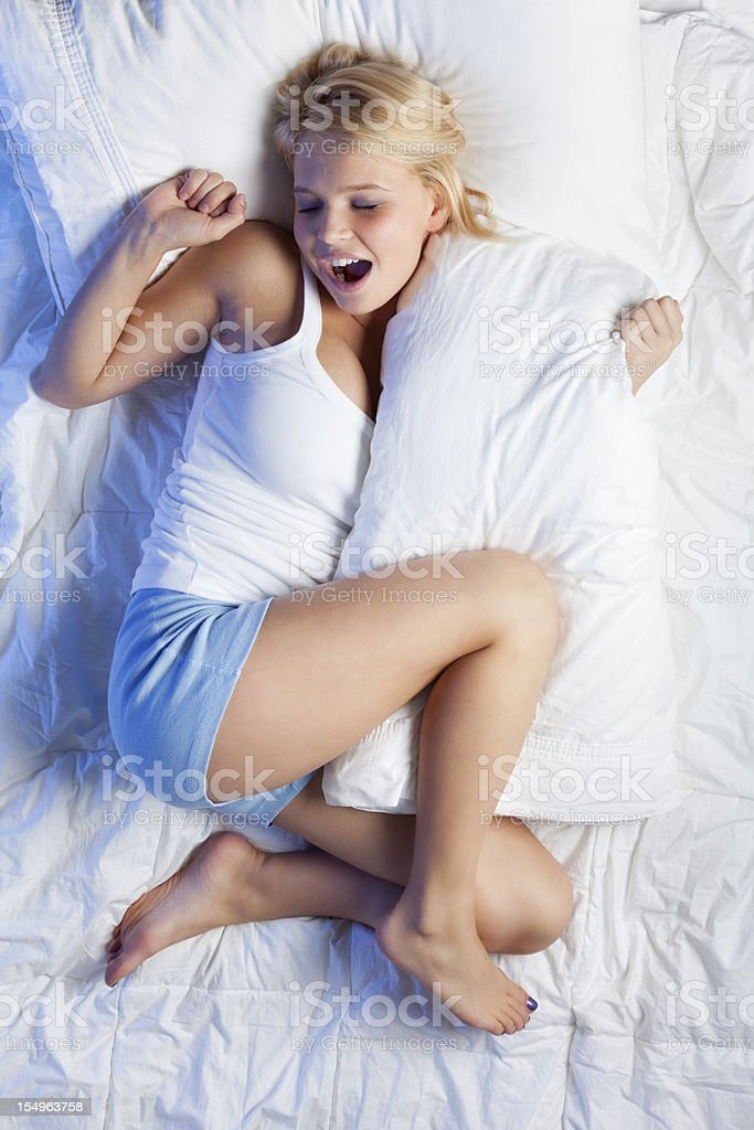 Attractive Young Woman on Bed Yawning royalty-free stock photo
