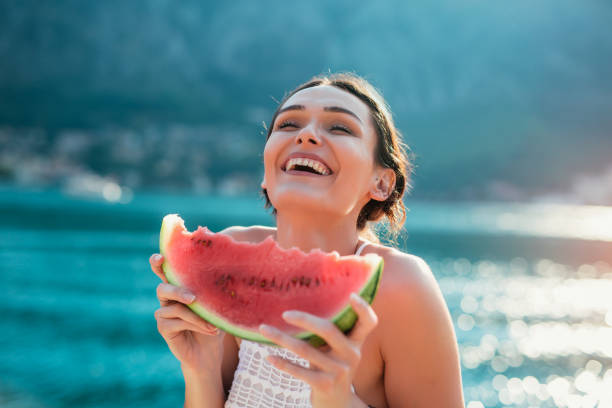 Attractive young woman on the beach eating watermelon stock photo
