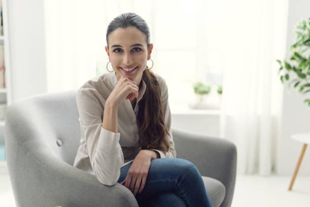Mulher jovem e atraente em casa posando ao lado de uma janela com a mão no queixo, ela está sentada na poltrona e sorrindo - foto de acervo