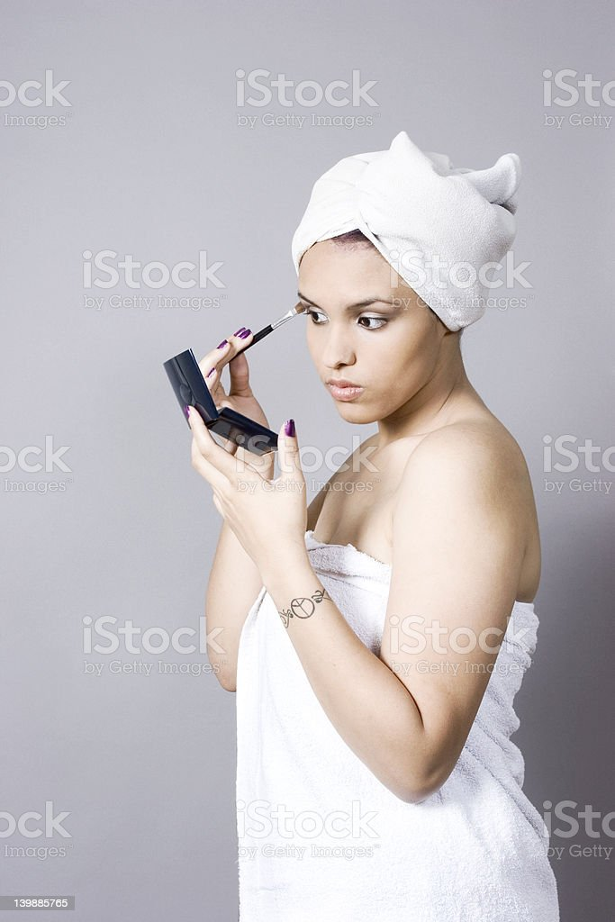 Attractive young woman putting on makeup royalty-free stock photo