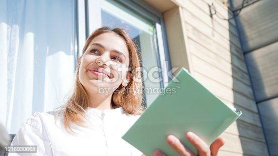 1176252245 istock photo Attractive young woman reading a book on her balcony on a sunny day. Beautiful girl wearing white shirt and holding a green book. 1216930665