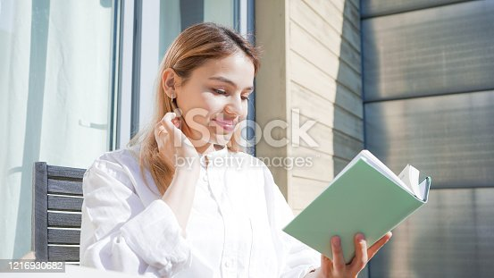 1176252245 istock photo Attractive young woman reading a book on her balcony on a sunny day. Beautiful girl wearing white shirt and holding a green book. 1216930682