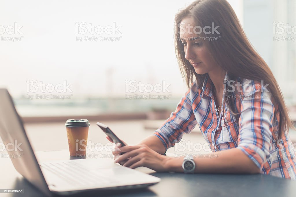 Attractive young woman reading a text message on her cell - foto stock