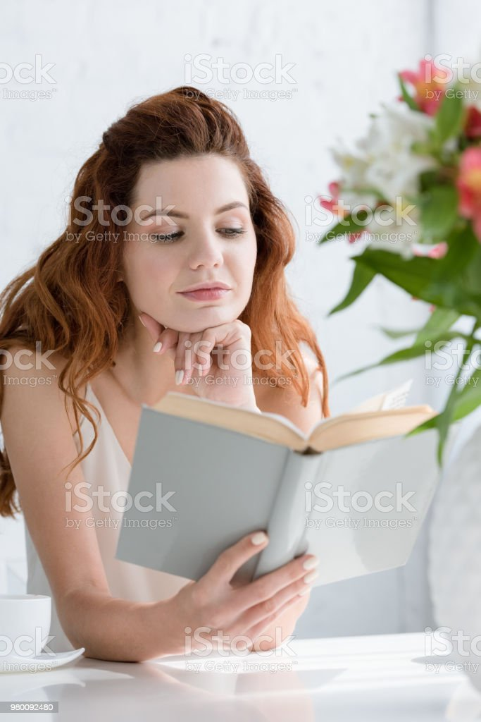attractive young woman reading book while sitting at table with coffee cup and flowers in vase stock photo