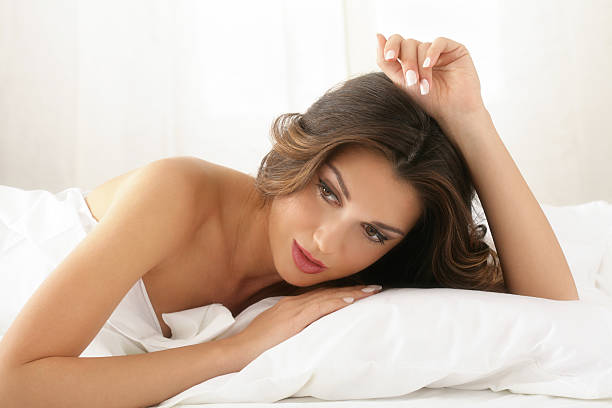 Attractive Young Woman Relaxing in Bed