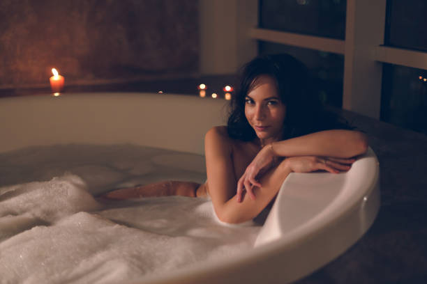 Attractive young woman relaxing taking a bath in luxury hotel room stock photo