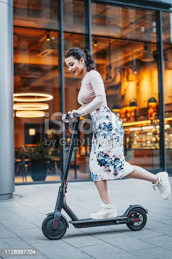 istock Attractive young woman riding a kick scooter at cityscape background. 1128997704