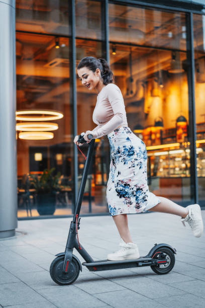 attractive young woman riding a kick scooter at cityscape background. - electric push scooter stock photos and pictures