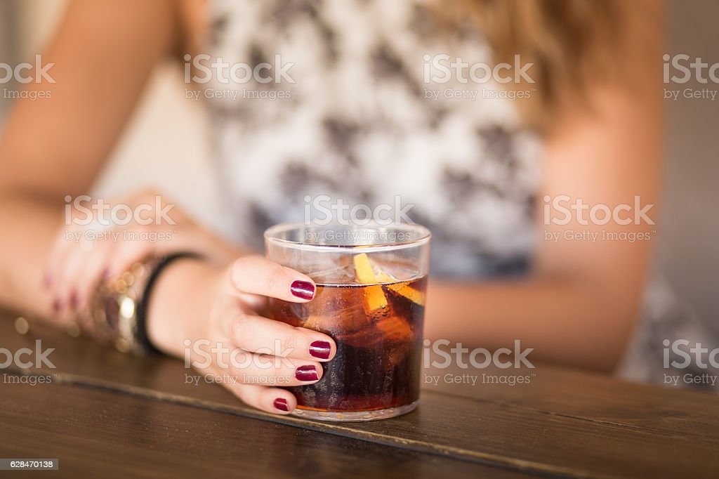 Attractive young woman seated at a terrace taking soda coke stock photo