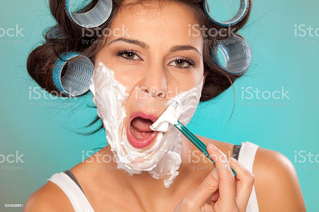 Attractive young woman shaving her face stock photo