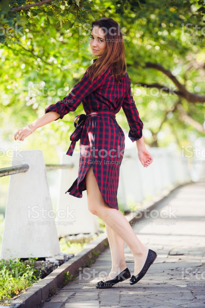 Attractive young woman shows her leg while walking in the park royalty-free stock photo
