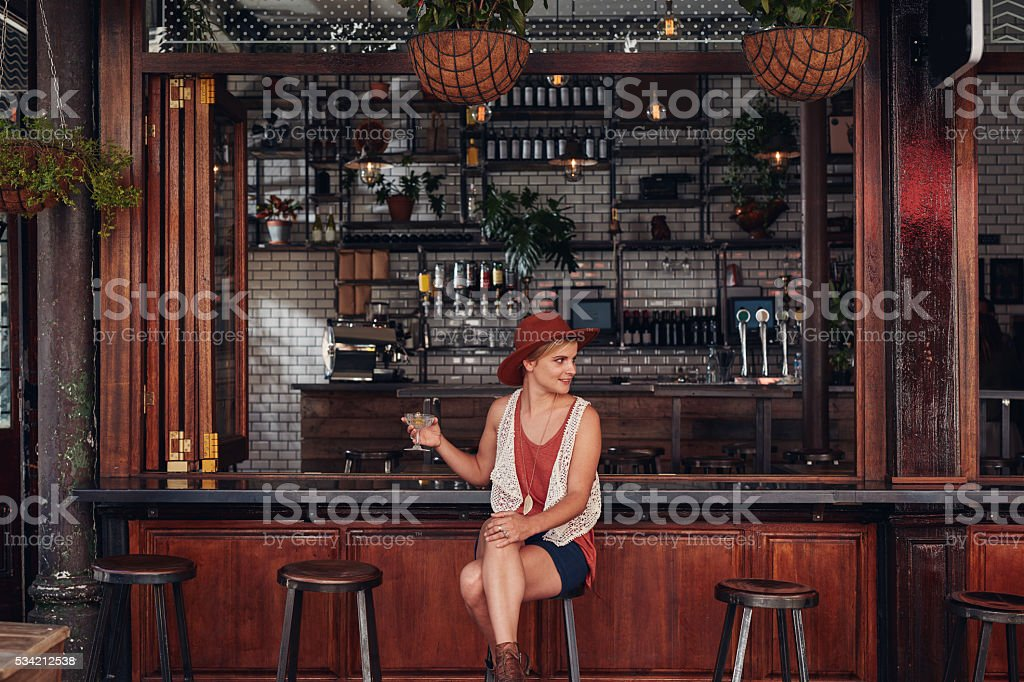 Attractive young woman sitting alone at a cafe stock photo